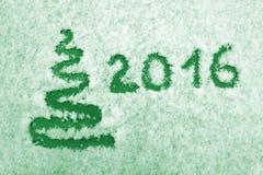 Übergeben Sie 2016 geschrieben und extrahieren Sie Weihnachtsbaum auf Schnee Neues Jahr und Weihnachtskarte Stockbild
