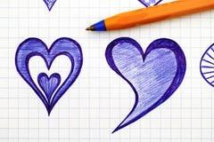Übergeben Sie gezogene Herzen auf Blatt des karierten Papiers mit Stift Stockfoto
