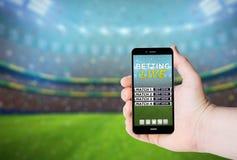 Übergeben Sie Griff ein Telefon mit dem Wetten online auf einem Schirm lizenzfreies stockbild