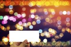 Übergeben Sie Griff Karte zur Partei mit buntem bokeh Hintergrund Lizenzfreies Stockbild