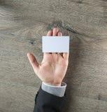 Übergeben Sie Griff leere Visitenkarte auf dunklem hölzernem Hintergrund Stockfotografie