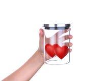 Übergeben Sie Griff rote Herzen im Glasgefäß mit Aluminiumdeckel Stockfotografie