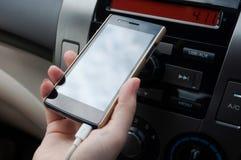 Übergeben Sie Griff Smartphone im Auto, Ladegerätsteckertelefon auf Auto Lizenzfreie Stockbilder