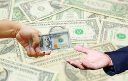 Übergeben Sie Griff viele US-Dollar mit US-Dollar Banknotenhintergrund Stockbild