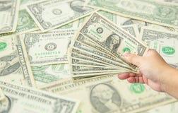 Übergeben Sie Griff viele US-Dollar mit US-Dollar Banknotenhintergrund Stockfotos