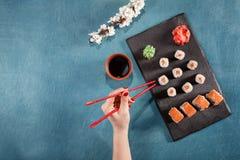 Übergeben Sie Griffessstäbchen auf Sushi mit Soße, Wasabi, Kirschblüte, Ingwer Stockfotos