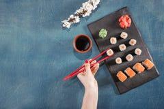 Übergeben Sie Griffessstäbchen auf Sushi mit Soße, Wasabi, Kirschblüte, Ingwer Lizenzfreie Stockbilder