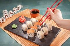 Übergeben Sie Griffessstäbchen mit Sushi auf schwarzem kochendem Schreibtisch Stockbilder