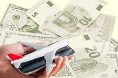 Übergeben Sie Griffhandy mit Flugzeugmodell auf Banknotenhintergrund Lizenzfreies Stockbild