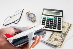 Übergeben Sie Griffhandy mit Flugzeugmodell auf Banknotenhintergrund Lizenzfreie Stockfotografie
