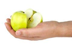 Übergeben Sie Holding den grünen Apfel, der zur Hälfte geschnitten wird Lizenzfreie Stockbilder