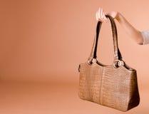 Übergeben Sie Holding lederne Handtasche auf dem beige Hintergrund Stockbild