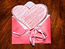 Übergeben Sie Holding rotes Valentinsgrußinneres auf schwarzem Hintergrund Lizenzfreies Stockbild