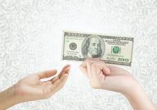 Übergeben Sie Holdinggelddollar und das Geben zum anderen Stockfoto