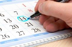 Übergeben Sie Kennzeichendatum im Kalender im Blau Stockbilder