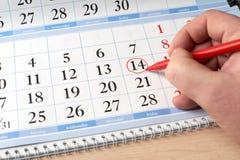 Übergeben Sie Kennzeichendatum am Kalender im Rot Stockbild