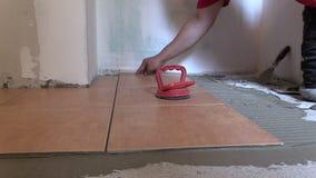 Übergeben Sie Kleber Keramikziegelscheibe auf Küchenboden stock footage