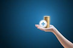 Übergeben Sie Münzen und die Ikone mit dem Pluszeichen Lizenzfreies Stockfoto