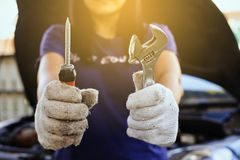Übergeben Sie Mechanikeringenieurfestlegung, den Autotechniker, der den Schraubenzieher und den Schlüssel, Konzeptwagenpflege häl Stockfotos