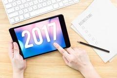 Übergeben Sie Notentablette mit 2017-jähriger Zahl auf Schirm mit Geschäft Stockfotos