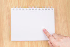Übergeben Sie Punkt zum leeren weißen Notizbuch auf hölzerne Tischplatte, Spott herauf FO Stockfoto