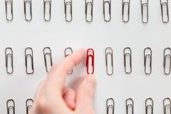 Übergeben Sie Sammeln unter Metallpapierklammern ein Rot, das zu anderen unterschiedlich ist lizenzfreies stockfoto