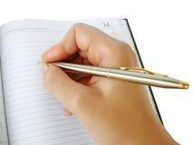 Übergeben Sie Schreiben in einem Notizbuch mit luxuriöser Feder Lizenzfreie Stockfotografie