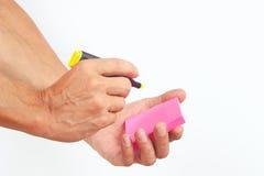 Übergeben Sie schriftliche Anmerkungen in der gelben Markierung auf einem rosa Aufkleber auf weißem Hintergrund Stockbilder