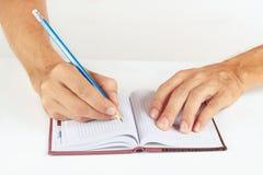 Übergeben Sie schriftliche Anmerkungen im Bleistift in einem Notizbuch auf weißem Hintergrund Lizenzfreie Stockbilder
