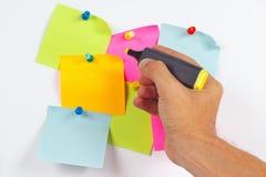 Übergeben Sie schriftlichen Anmerkungen eine gelbe Markierung auf einem roten Aufkleber auf weißem Brett von der Mitteilung Stockfoto