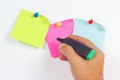 Übergeben Sie schriftlichen Anmerkungen eine grüne Markierung auf einem roten Aufkleber auf weißem Brett von der Mitteilung Lizenzfreie Stockbilder