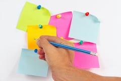 Übergeben Sie schriftlichen Anmerkungen einen Bleistift auf einem Aufkleber auf weißem Anschlagbrett Stockfotos