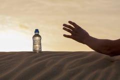 Übergeben Sie Versuch, um die Flasche des Wassers auf Sandwüste zu fangen Stockfotos