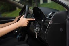 Übergeben Sie woamn Fahrer, der Blinkerwarnlicht im Auto verwendet Stockfoto