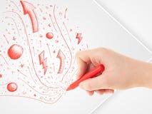 Übergeben Sie zeichnende abstrakte Skizzen und Gekritzel auf Papier Stockfotos
