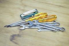 Übergeben Sie Zupacken, den Griff, der, die rostigen Werkzeuge alt ist, die auf einem Holztisch liegen Stockfotografie