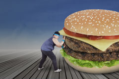 Übergewichtiger Mensch, der großen Burger drückt stockbilder