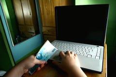 Übergibt das Halten des Geldes beim Arbeiten an einem Computerlaptop Stockfotografie