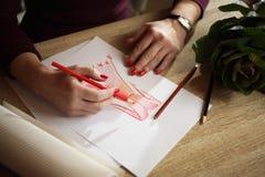 Übergibt die erwachsene Frau, die eine Bleistiftskizze des Kleides darstellt Lizenzfreie Stockfotos