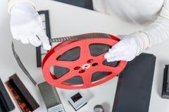 Übergibt die Frau, die roten Film der Spule 16mm hält Lizenzfreies Stockbild