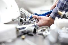 Übergibt Klempner bei der Arbeit in einem Badezimmer und plombiert Reparaturservice, wie Lizenzfreie Stockfotos
