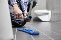 Übergibt Klempner bei der Arbeit in einem Badezimmer und plombiert Reparaturservice, wie Stockfotografie