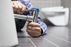 Übergibt Klempner bei der Arbeit in einem Badezimmer und plombiert Reparaturservice, wie Lizenzfreies Stockbild