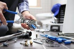 Übergibt Klempner bei der Arbeit in einem Badezimmer und plombiert Reparaturservice, wie Lizenzfreies Stockfoto