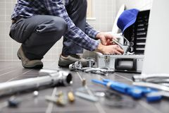 Übergibt Klempner bei der Arbeit in einem Badezimmer und plombiert Reparaturservice, wie Lizenzfreie Stockfotografie