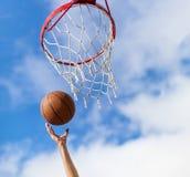 Übergibt werfenden Basketballball in Korb Stockbild