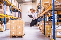 Überglückliche Arbeitnehmerin oder Aufsichtskraft in einem Lager lizenzfreie stockfotos