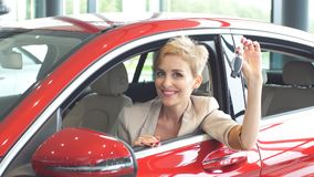 Überglückliche Fahrerfrau, die neuen Schlüssel beim Sitzen im Autosalon lächelt und zeigt