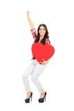 Überglückliche Frau, die ein großes rotes Herz hält Stockfotos