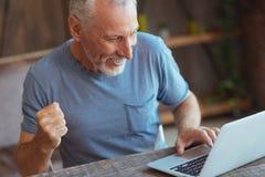 Überglücklicher gealterter Mann, der seinen Laptop verwendet Lizenzfreie Stockbilder